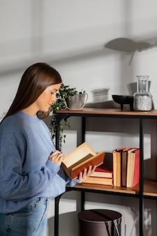 Vue de face de la belle femme lisant un livre