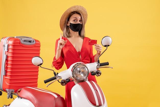 Vue de face de la belle femme avec un masque noir tenant une carte de crédit près de cyclomoteur et valise rouge