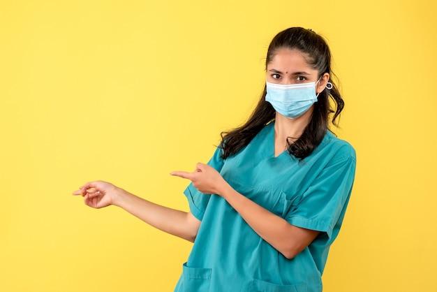 Vue de face belle femme médecin en uniforme pointant sur fond jaune