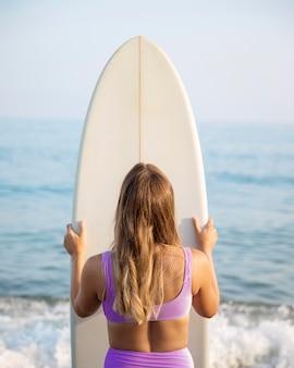 Vue de face de la belle femme avec planche de surf