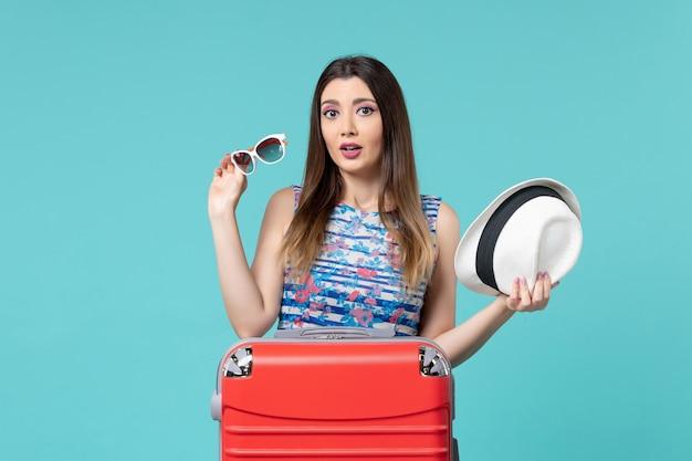 Vue De Face Belle Femme Préparant Pour Les Vacances Tenant Des Lunettes De Soleil Et Un Chapeau Sur L'espace Bleu Photo gratuit