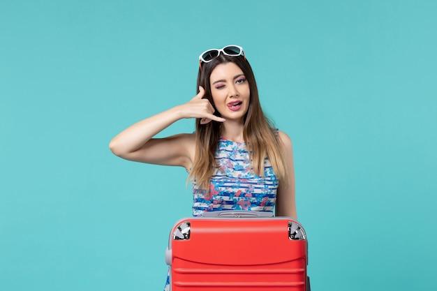 Vue de face belle femme préparant pour le voyage montrant l'indicatif d'appel téléphonique sur l'espace bleu
