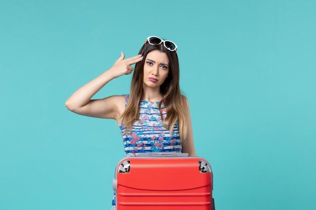 Vue de face belle femme prépare pour le voyage avec son gros sac rouge sur fond bleu mer vacances voyage voyage voyage fille