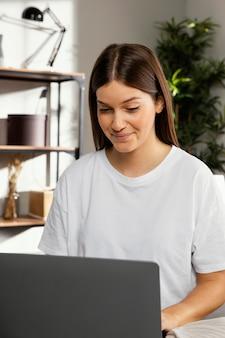 Vue de face de la belle femme restant sur ordinateur portable