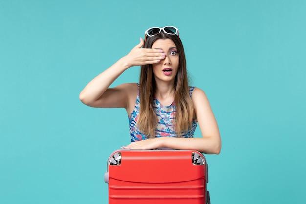 Vue De Face Belle Femme Se Préparant Pour Des Vacances Sur Un Espace Bleu Clair Photo gratuit
