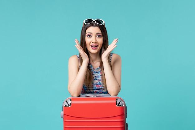 Vue de face belle femme se préparant pour des vacances sur un espace bleu clair