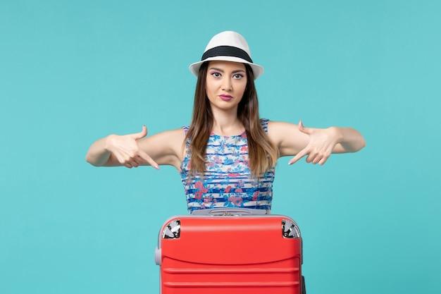 Vue de face belle femme se préparant pour les vacances et posant sur un espace bleu clair
