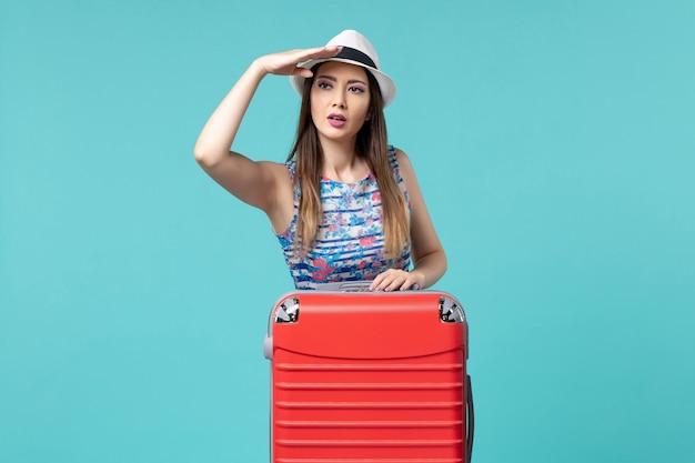 Vue de face belle femme se préparant pour les vacances posant sur l'espace bleu