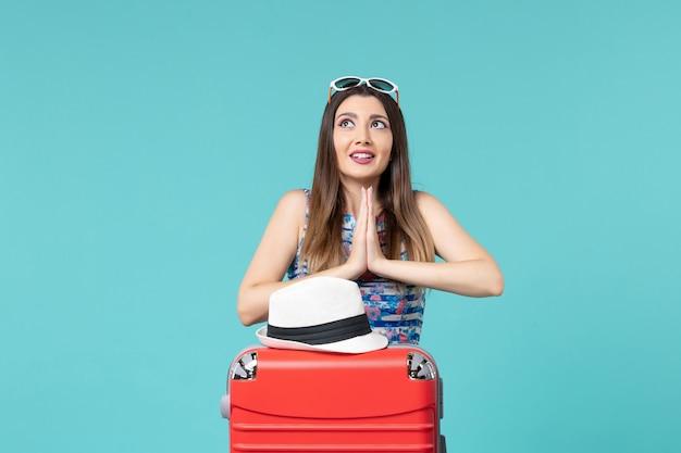 Vue De Face Belle Femme Se Préparant Pour Les Vacances Avec Sac Et Chapeau Sur L'espace Bleu Photo gratuit