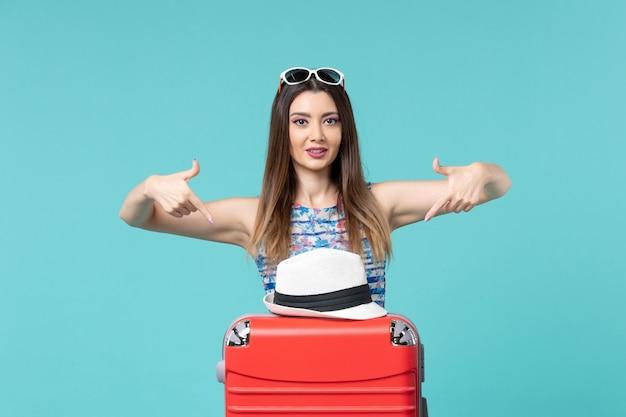 Vue de face belle femme se préparant pour les vacances avec sac et chapeau sur l'espace bleu