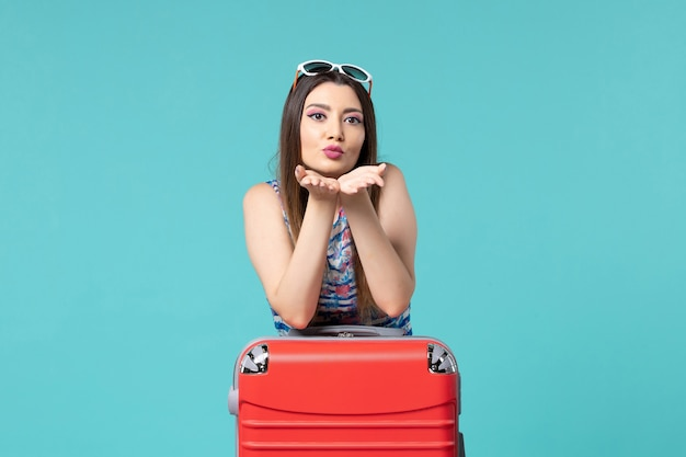 Vue de face belle femme se préparant pour des vacances avec un sac rouge sur un espace bleu clair