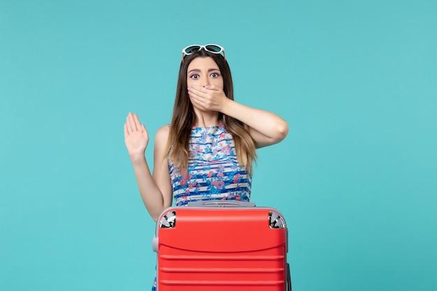 Vue De Face Belle Femme Se Préparant Pour Le Voyage Avec Son Gros Sac Rouge Sur L'espace Bleu Clair Photo gratuit