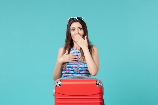 Vue de face belle femme se préparant pour le voyage avec son gros sac rouge sur l'espace bleu clair