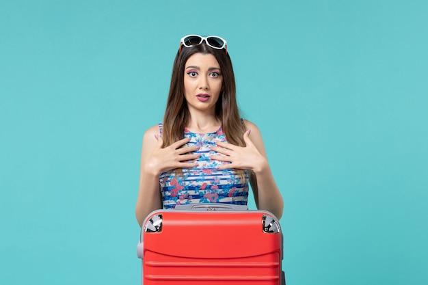 Vue de face belle femme se préparant pour le voyage avec son gros sac rouge sur l'espace bleu