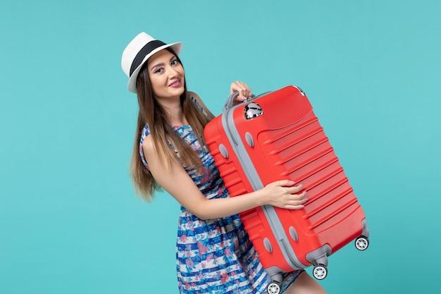 Vue de face belle femme tenant le sac et préparation pour le voyage sur l'espace bleu