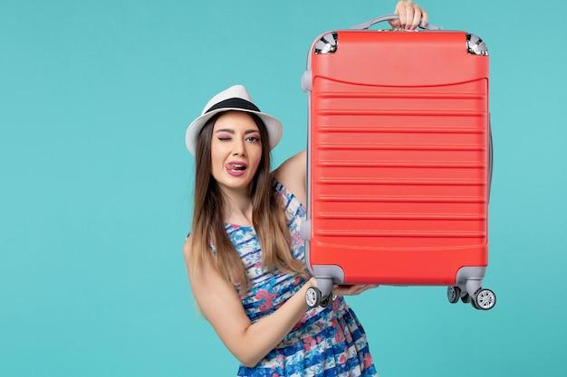 Vue de face belle femme tenant sac et préparation pour le voyage sur le plancher bleu voyage vacances voyage voyage mer