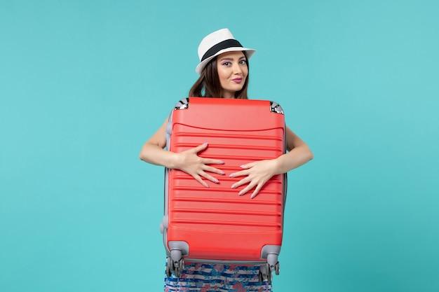 Vue de face belle femme tenant un sac rouge et se préparant pour le voyage sur l'espace bleu