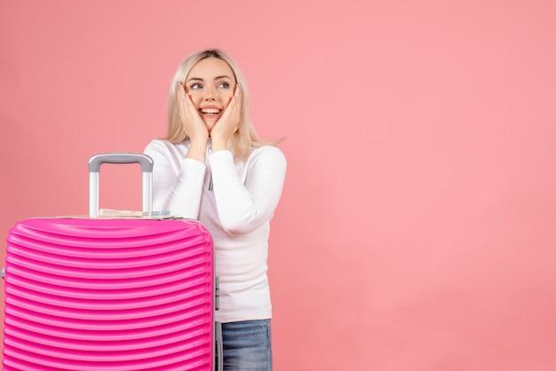 Vue de face belle femme avec valise rose mettant les mains sur sa joue