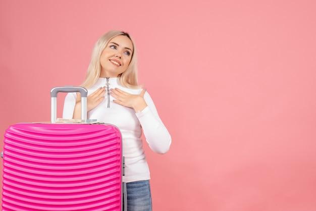 Vue de face belle femme avec valise rose mettant les mains sur sa poitrine
