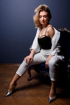 Vue de face d'une belle femme vêtue d'un costume blanc rayé assis sur la chaise sur le fond bleu du mur
