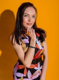 Vue de face d'une belle femme vêtue d'une robe colorée debout sur le mur jaune isolé