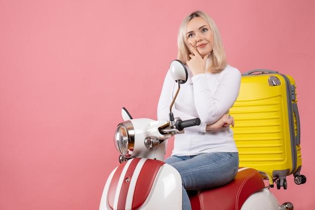Vue de face belle fille blonde sur un cyclomoteur mettant la main sur son menton