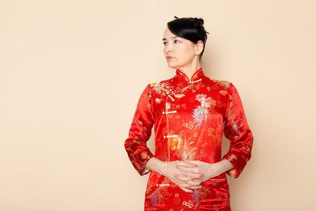 Une vue de face belle geisha japonaise en robe japonaise rouge traditionnelle avec des bâtons de cheveux posant debout sur la cérémonie de fond crème divertissant le japon est