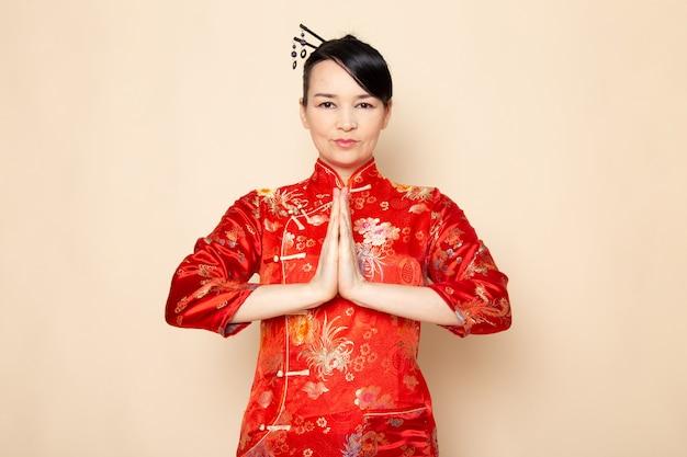 Une vue de face belle geisha japonaise en robe japonaise rouge traditionnelle avec des bâtons de cheveux posant avec ses mains debout sur la cérémonie de fond crème divertissant le japon est