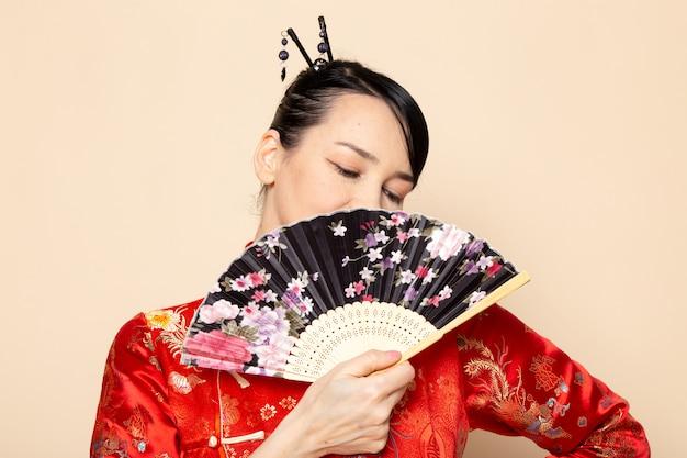 Une vue de face belle geisha japonaise en robe japonaise rouge traditionnelle avec des bâtons de cheveux posant tenant un ventilateur pliant souriant sur la cérémonie de fond crème japon