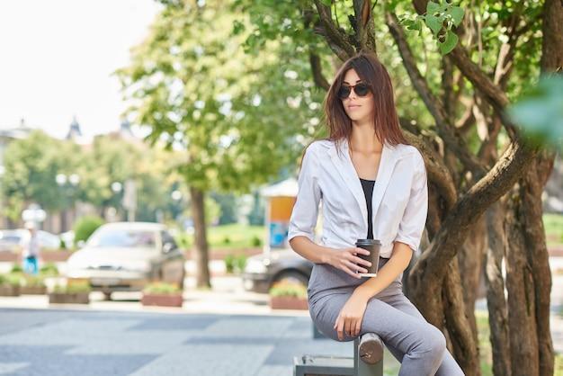 Vue de face de la belle jeune étudiante assise sur un banc en bois.