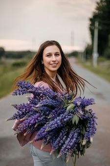 Vue de face de la belle jeune fille brune debout sur une route de banlieue avec un gros bouquet de lupins violets sauvages