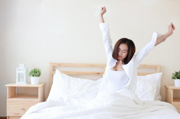 Vue de face belle et saine jeune femme asiatique se réveiller le matin, elle s'étire après le réveil le matin sur un lit blanc dans la chambre