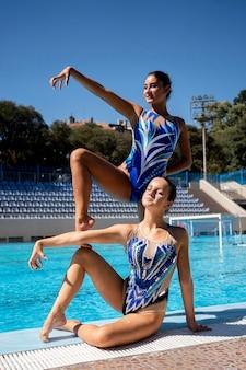 Vue de face de belles filles posant au bord de la piscine