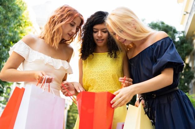 Vue de face de belles filles avec sac à provisions