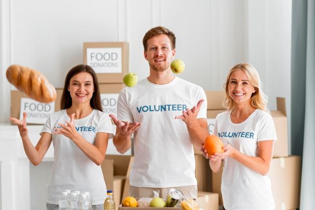 Vue de face de bénévoles smiley aidant avec des dons alimentaires