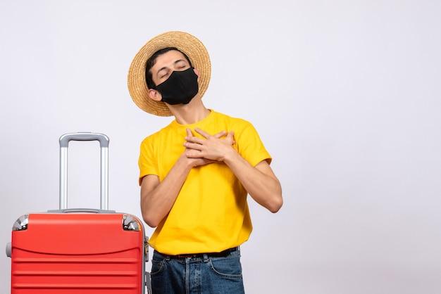 Vue de face béni jeune homme avec t-shirt jaune et valise rouge mettant les mains sur sa poitrine