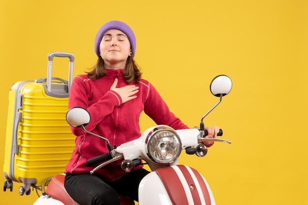 Vue de face bénie jeune femme sur cyclomoteur mettant la main sur sa poitrine