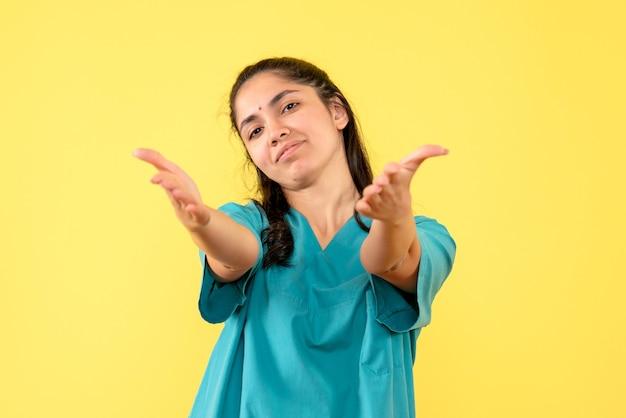Vue de face bienheureuse jolie femme médecin ouvrant ses mains debout sur fond jaune