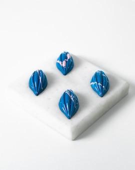 Vue de face bleu pierres brillantes isolées sur l'éponge blanche et le sol