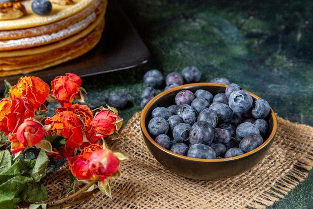 Vue de face bleuets frais avec un délicieux gâteau au miel surface sombre