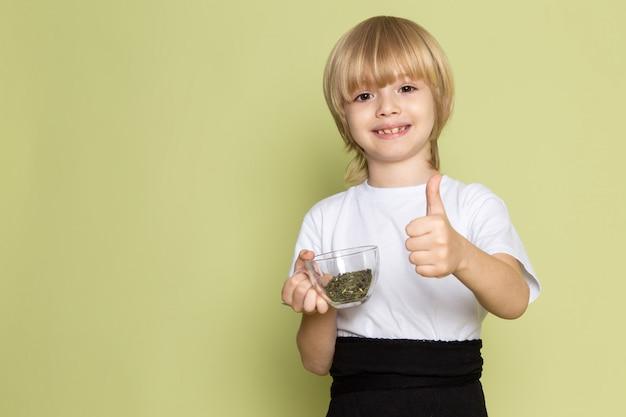 Une vue de face blond mignon garçon en t-shirt blanc tenant des espèces sur le bureau de couleur pierre