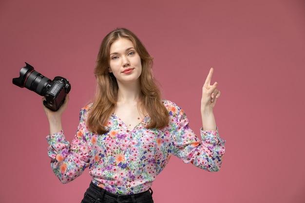 Vue de face blonde lady donnant une pose avec photocamera sur mur rose