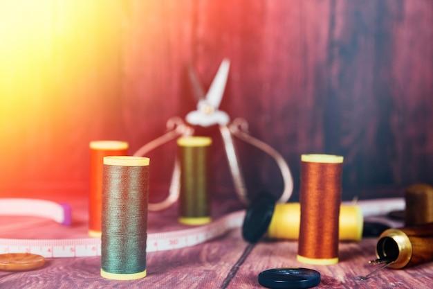 Vue de face des bobines de fil orange et vert. en arrière-plan, des ciseaux de couture vintage avec un éclat de lumière.
