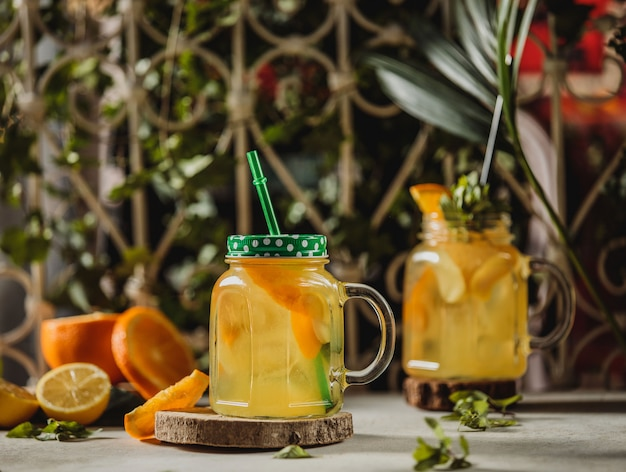 Vue de face de boisson limonade avec tranches d'orange et de citron dans un verre à cocktail avec poignée et paille sur un support en bois sur la table
