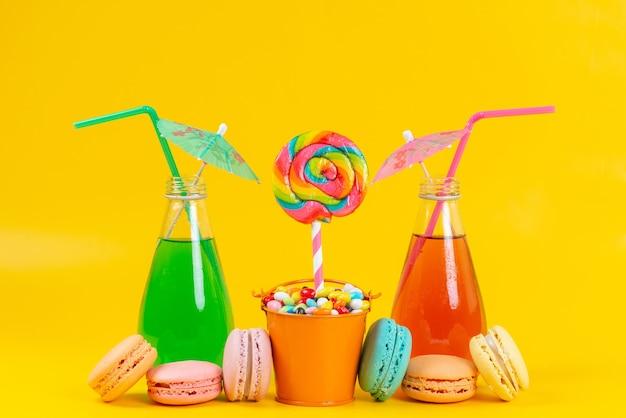 Une vue de face des boissons et des macarons colorés et délicieux avec des sucettes et des bonbons sur jaune