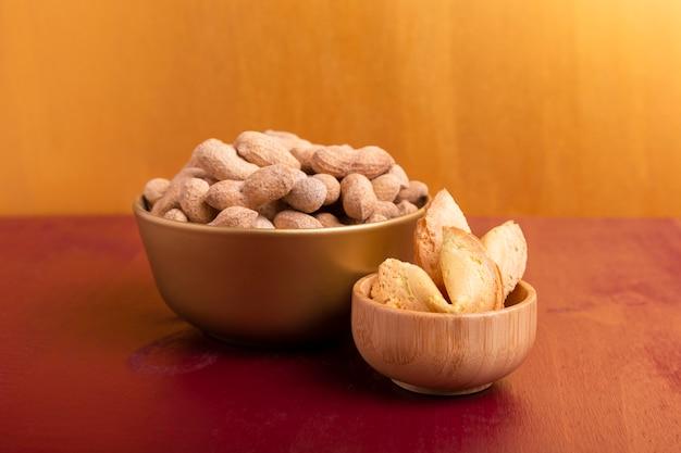 Vue de face de bols de cacahuètes et biscuits de fortune pour le nouvel an chinois
