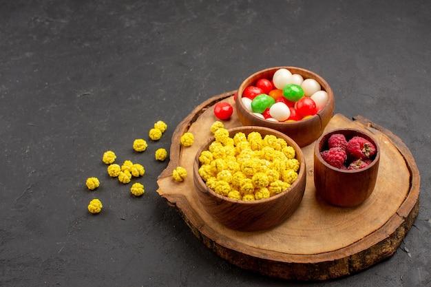 Vue de face des bonbons colorés sur du thé au sucre candi de couleur sombre