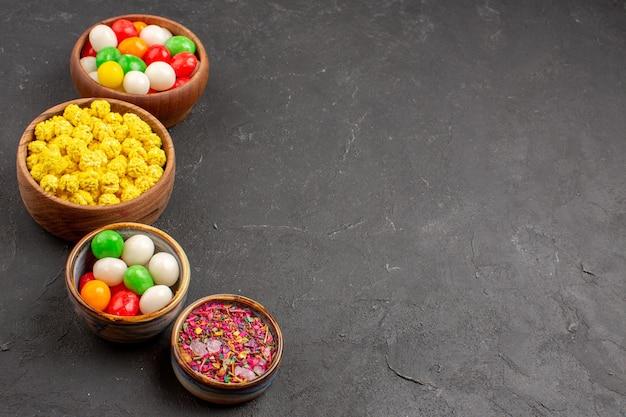 Vue de face des bonbons colorés sur un espace sombre