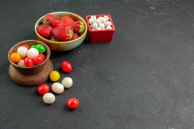 Vue de face de bonbons colorés avec des fraises