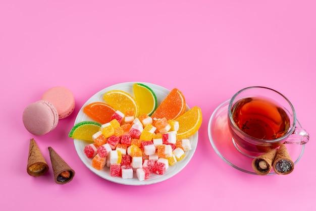 Une vue de face des bonbons colorés et des marmelades pour l'heure du thé sur rose, sucre sucré de confiture de thé